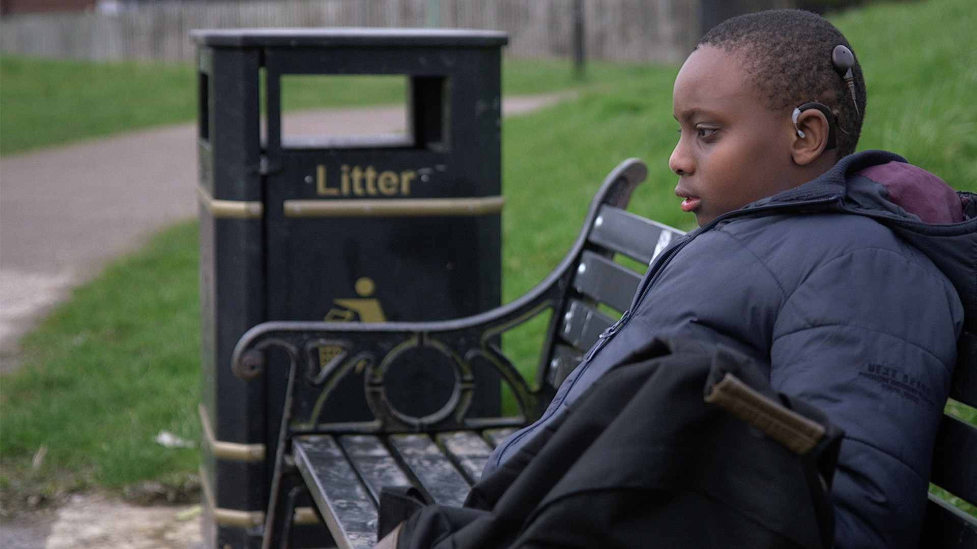 Boy with hearing aids sits on a park bench